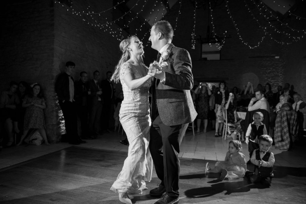 laughing bride groom enjoy first dance kingscote barn tetbury oxford wedding photography