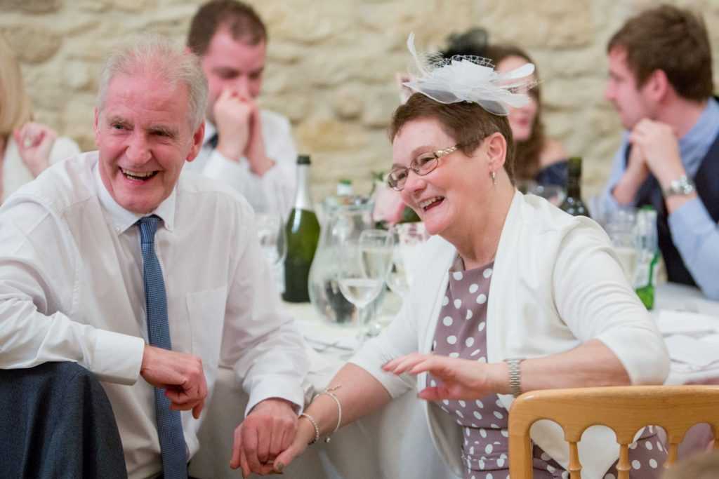 laughing elderly guest reception dinner kingscote barn tetbury oxford wedding photographers
