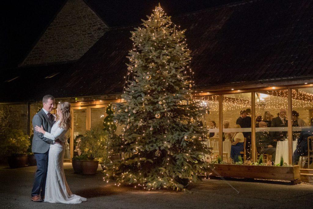 bride groom beside christmas tree kingscote barn tetbury oxfordshire wedding photographer