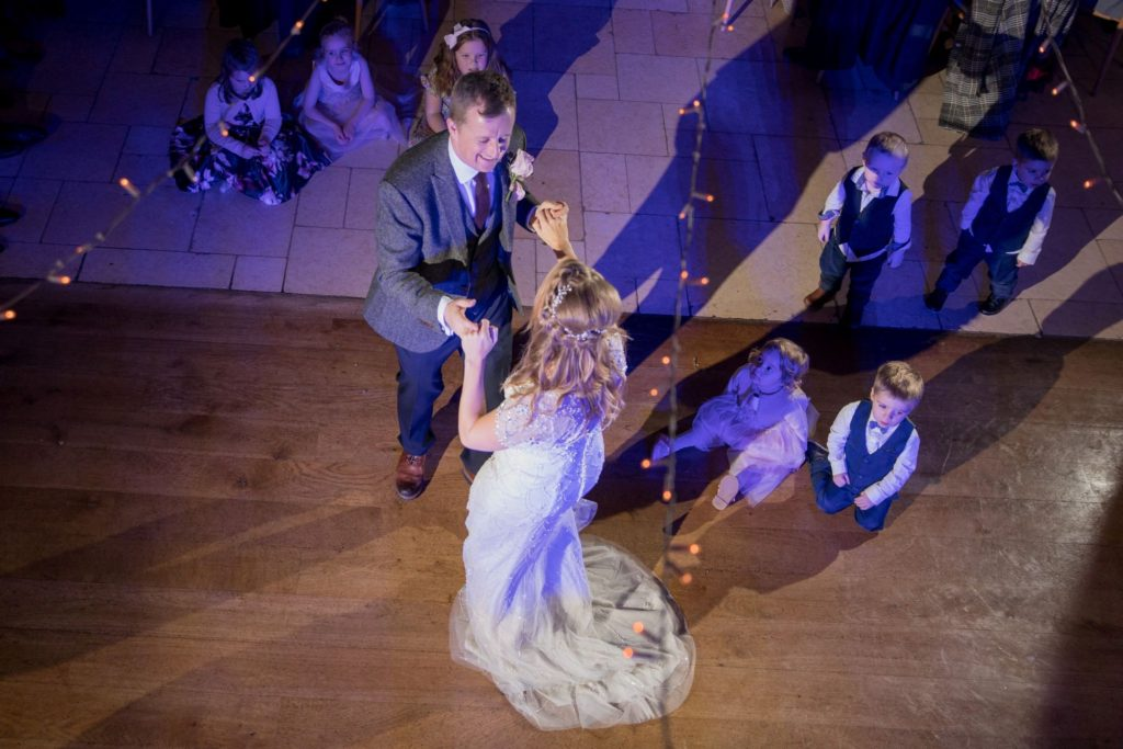 young guests watch first dance kingscote barn tetbury oxfordshire wedding photographers