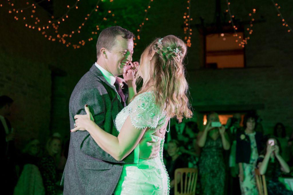 smiling bride and groom dance kingscote barn tetbury oxford wedding photographer