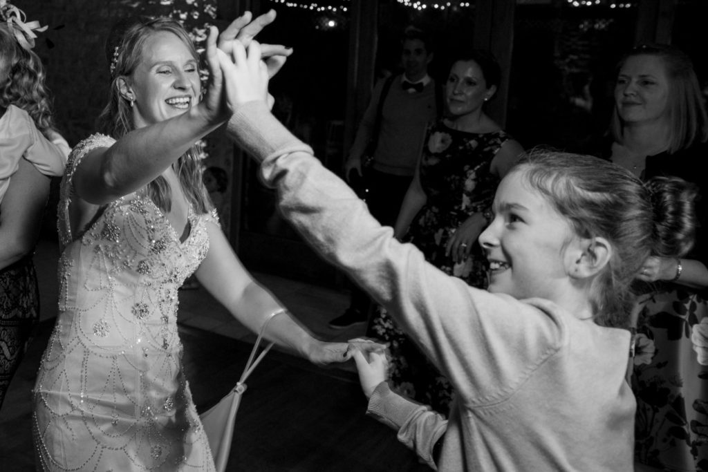 bride dances with young guest kingscote barn tetbury oxford wedding photography