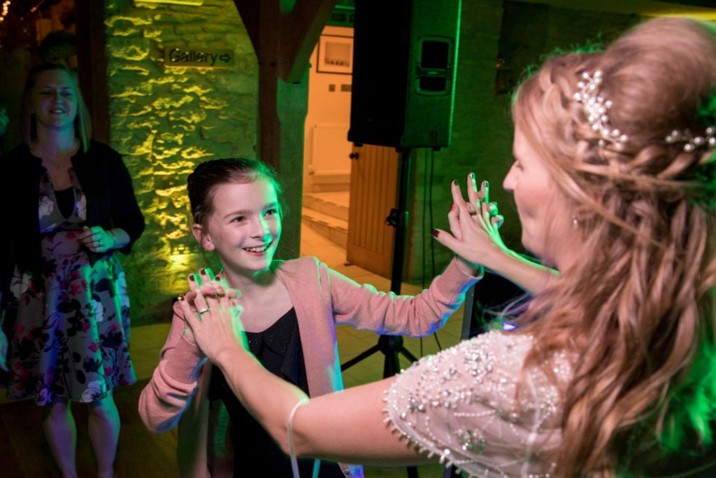 young guest dances with bride kingscote barn tetbury oxfordshire wedding photographer