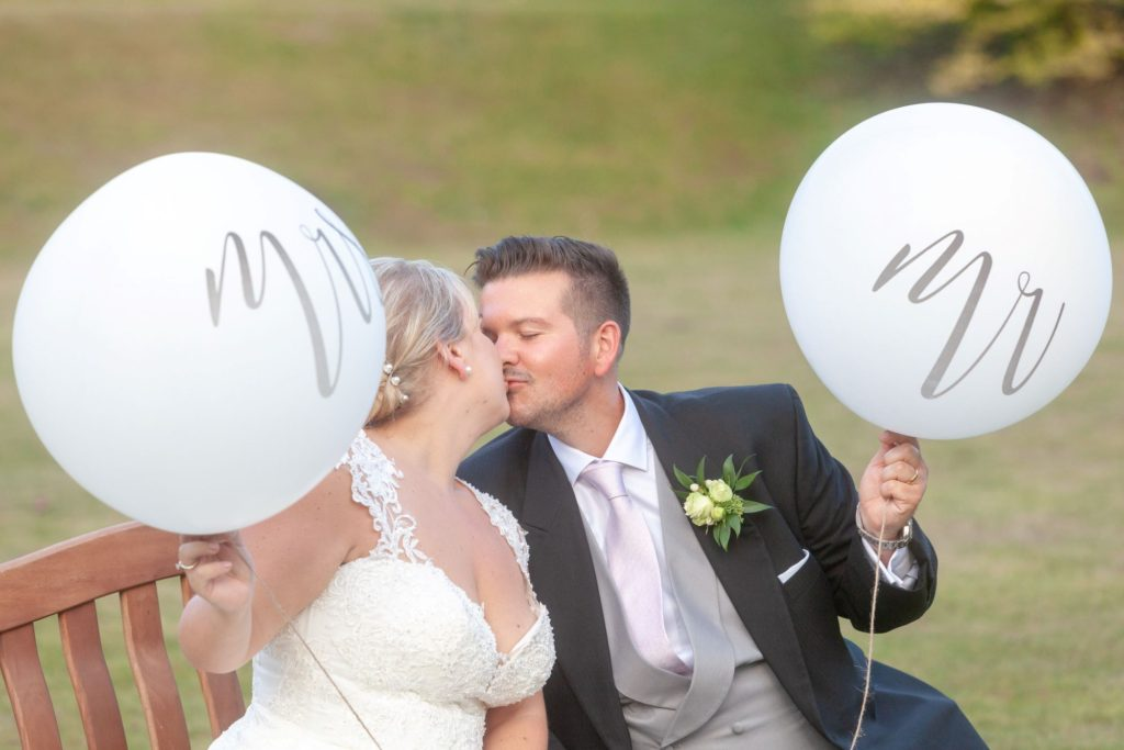 bride groom kiss with Mr and Mrs balloons stately home venue oxford wedding photographers