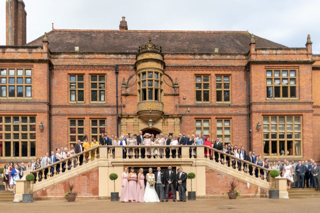 guests pose for traditional photograph stately home venue oxfordshire wedding photographer
