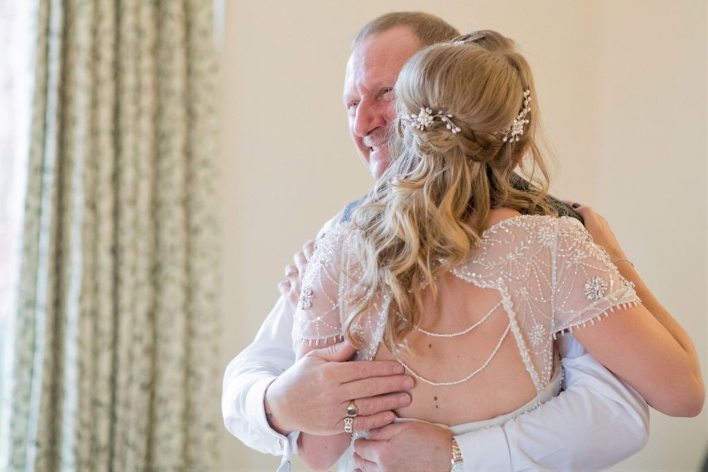 father hugs bride kingscote barn venue tetbury oxfordshire wedding photographers