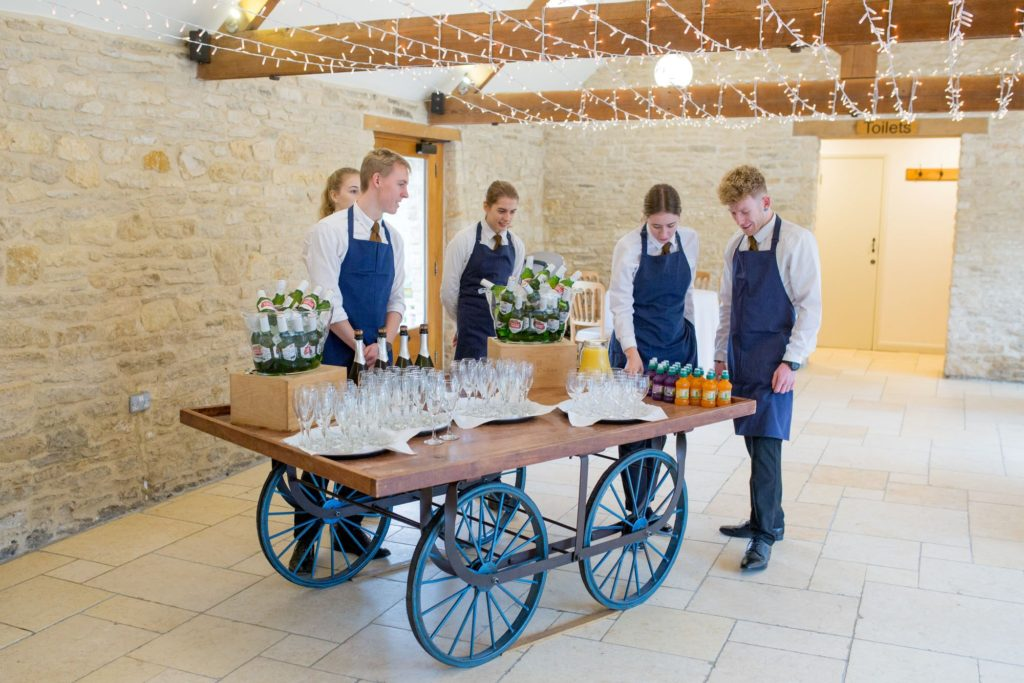 staff prepare guests champagne kingscote barn venue oxford wedding photographers