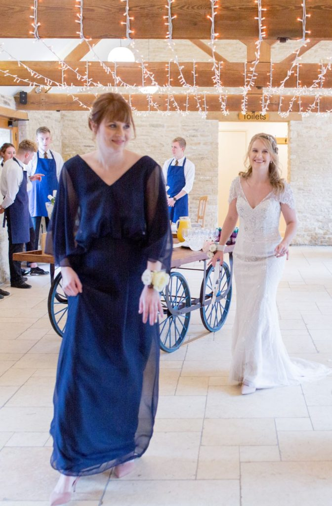 bride and bridesmaid before marriage ceremony kingscote barn tetbury oxfordshire wedding photographer