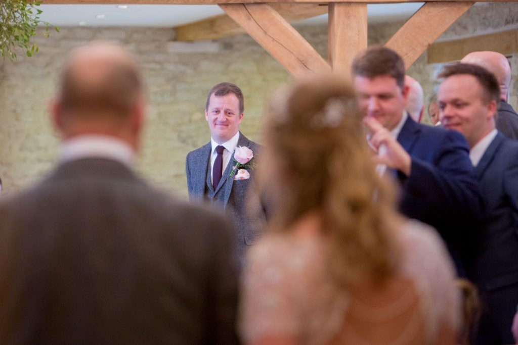 grooms first look at bride marriage ceremony kingscote barn tetbury oxfordshire wedding photography