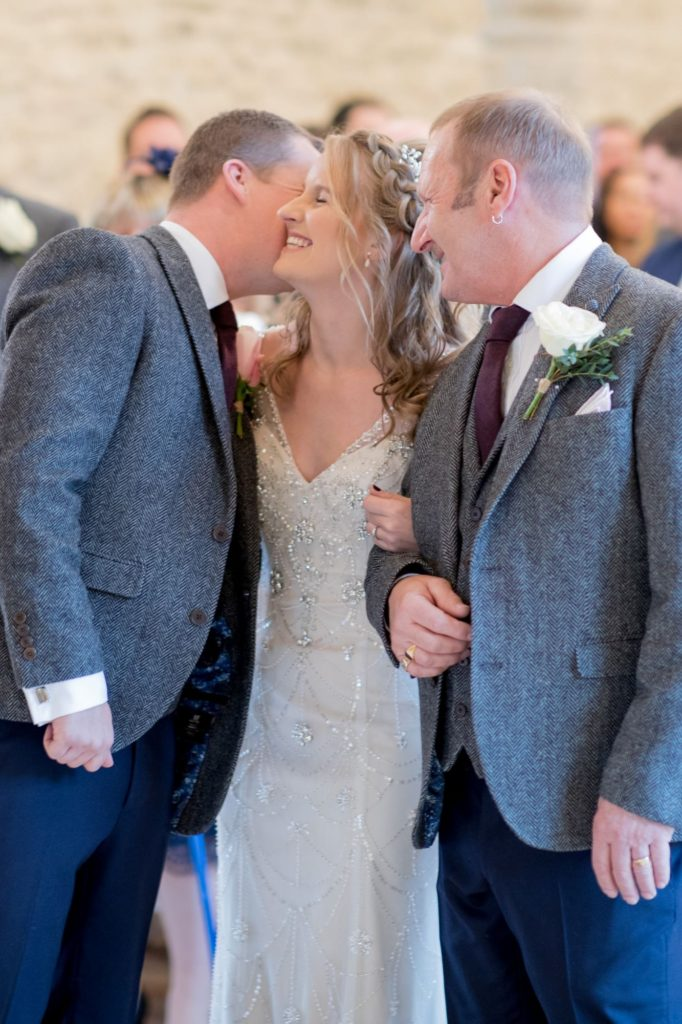 father of the bride with bride kisses groom kingscote barn tetbury oxford wedding photographers
