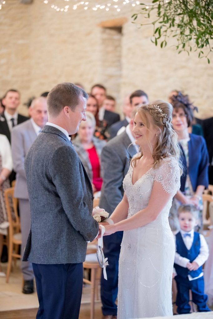 bride and groom under misletoe kingscote barn marriage ceremony oxford wedding photographer