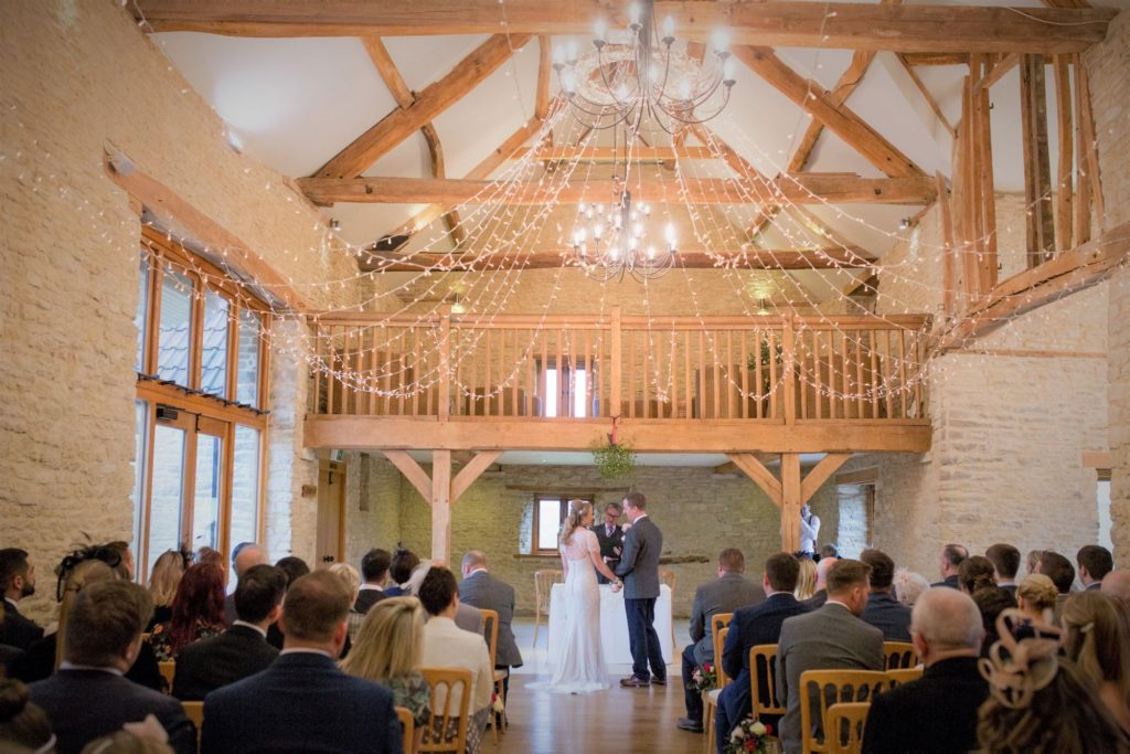 bride groom marriage ceremony kingscote barn venue tetbury oxfordshire wedding photographer