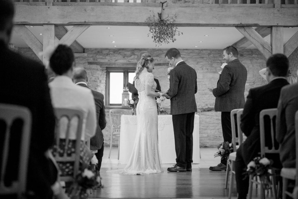 bride and groom exchange rings kingscote barn tetbury oxfordshire wedding photography