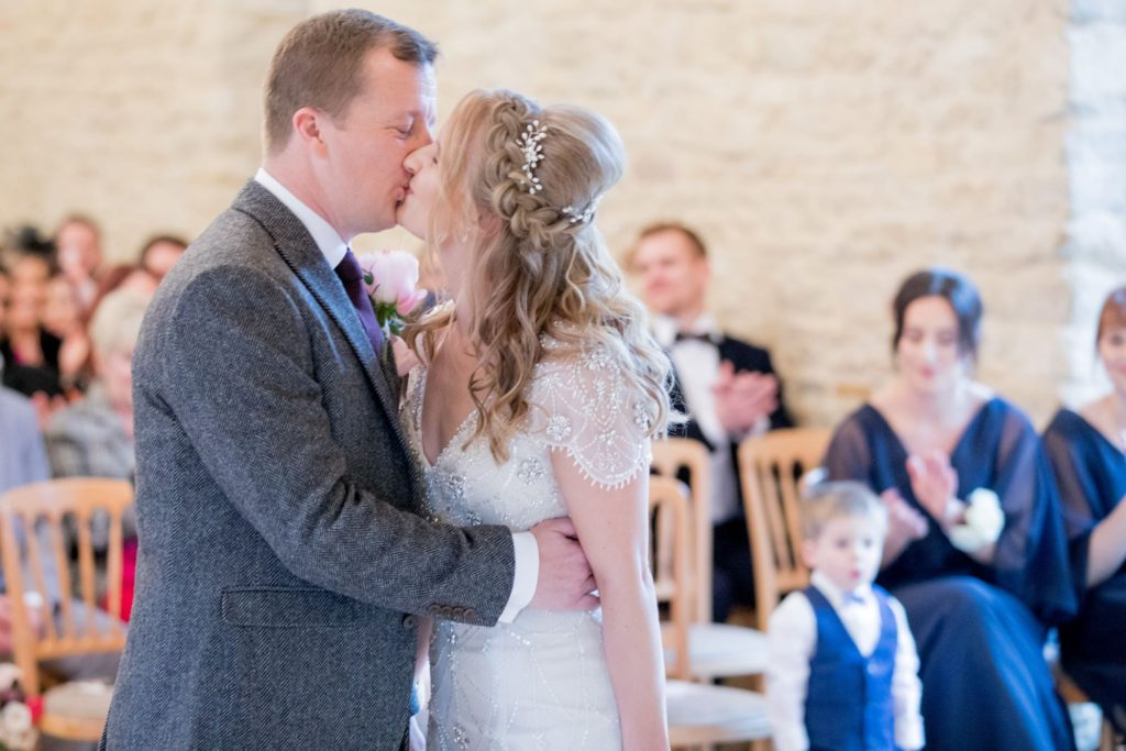 bride and groom first kiss kingscote barn marriage ceremony oxford wedding photographers