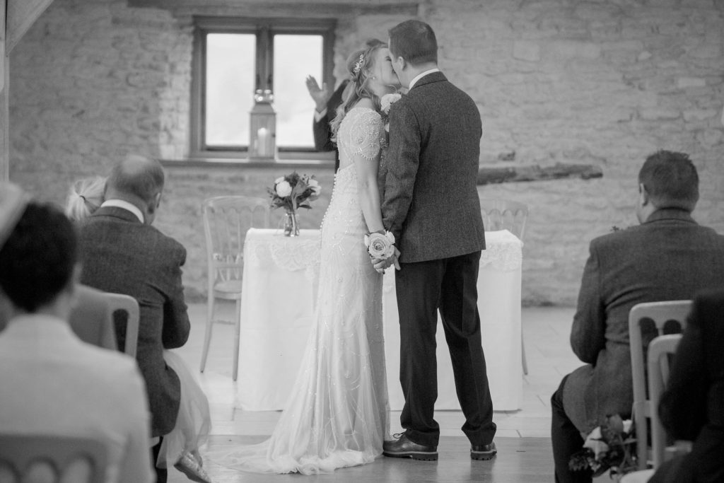 bride groom marriage ceremony kiss kingscote barn tetbury oxford wedding photography