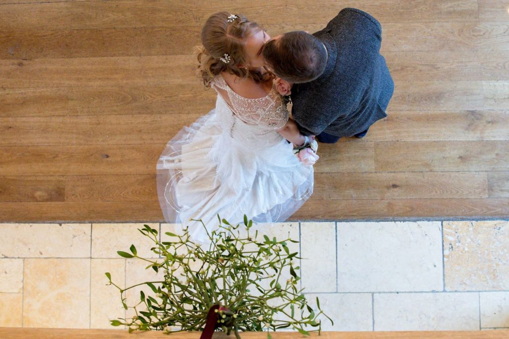bride groom kiss under misletoe kingscote barn tetbury oxfordshire wedding photographers