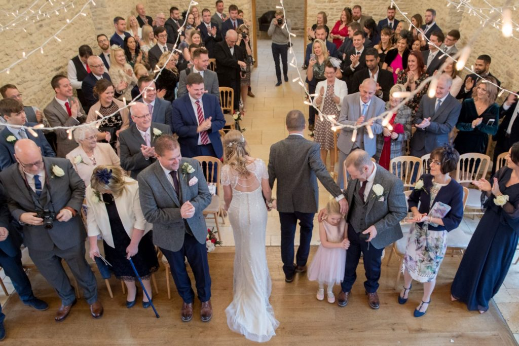 bride groom walk down aisle kingscote barn tetbury oxfordshire wedding photography