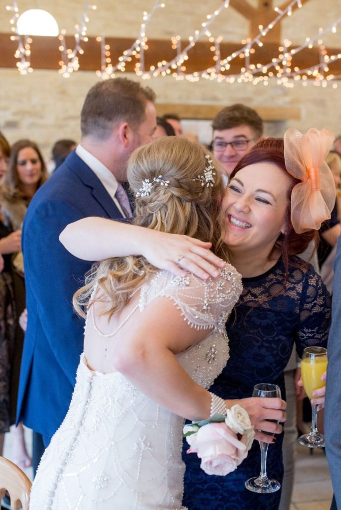 bride hugs smiling guest reception kingscote barn tetbury oxford wedding photographers