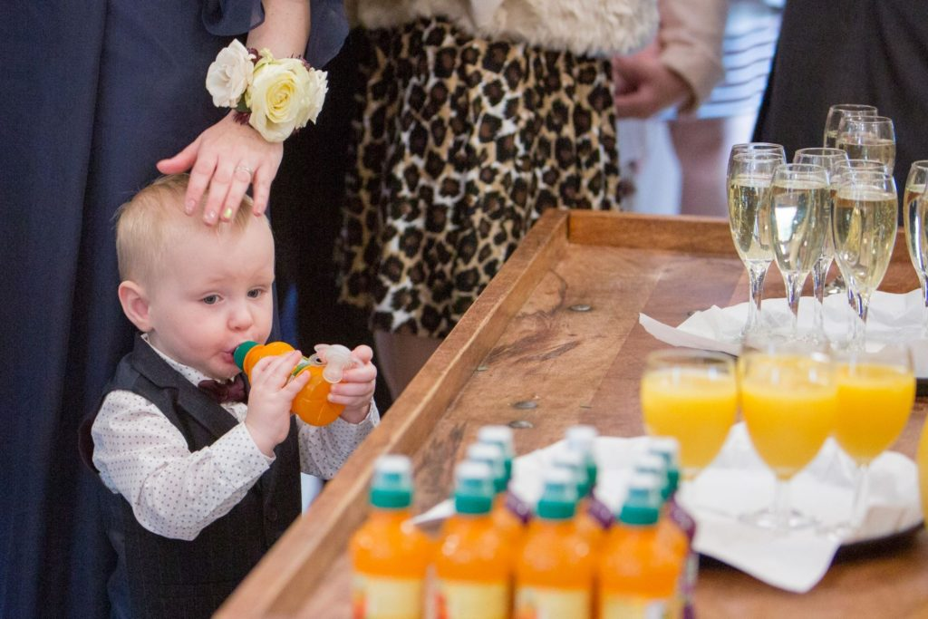 toddler enjoys orange drink reception kingscote barn tetbury oxford wedding photography
