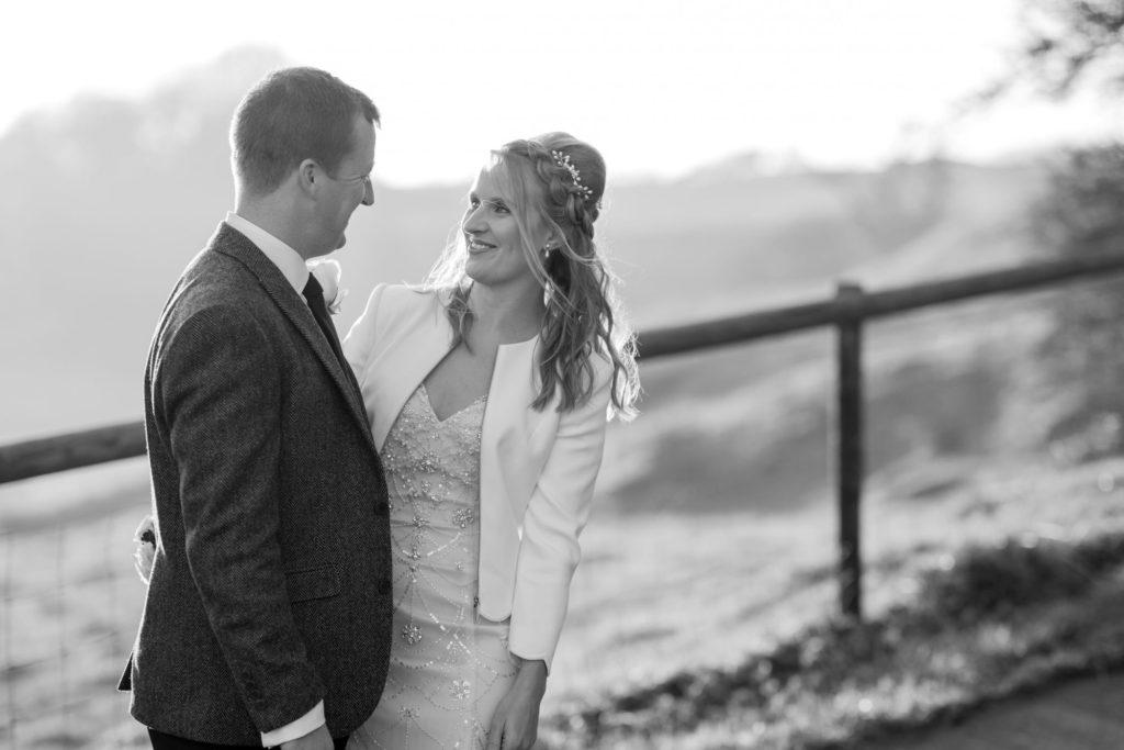 bride groom lovingly looks kingscote barn grounds tetbury oxford wedding photographer