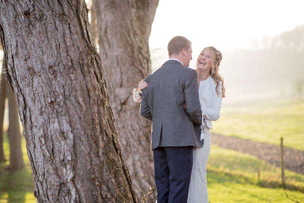 laughing bride groom sunset kingscote barn tetbury oxfordshire wedding photographer