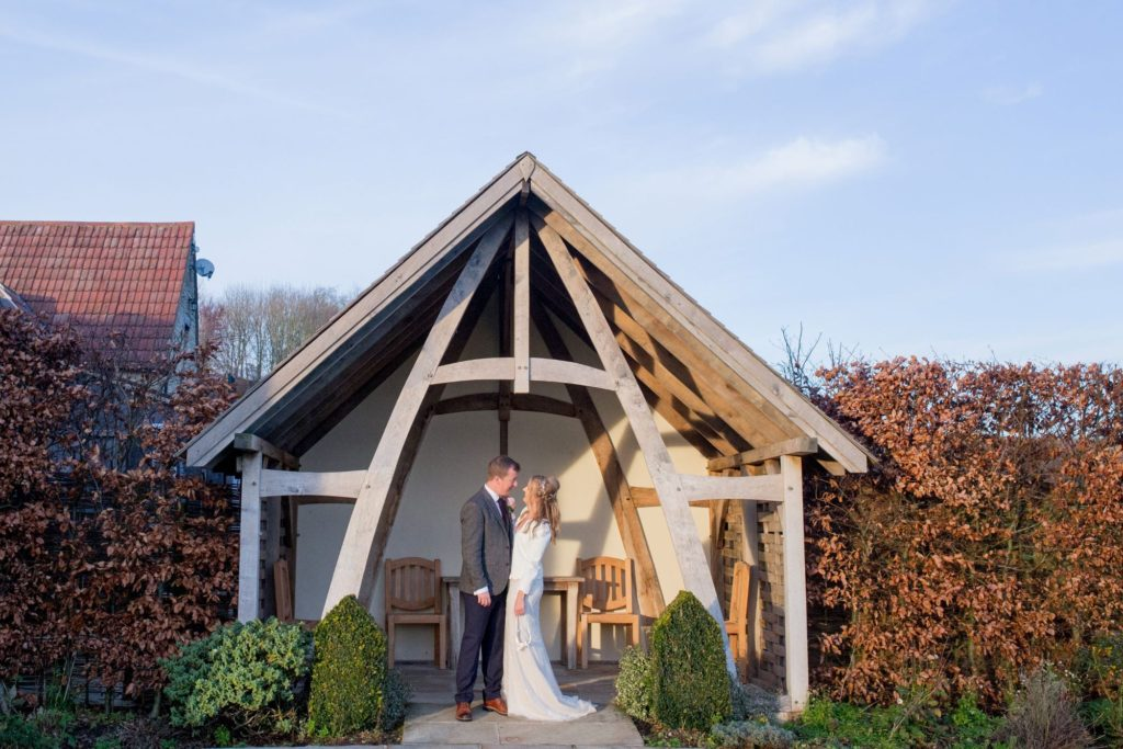 bride groom under wooden arch kingscote barn grounds tetbury oxfordshire wedding photography