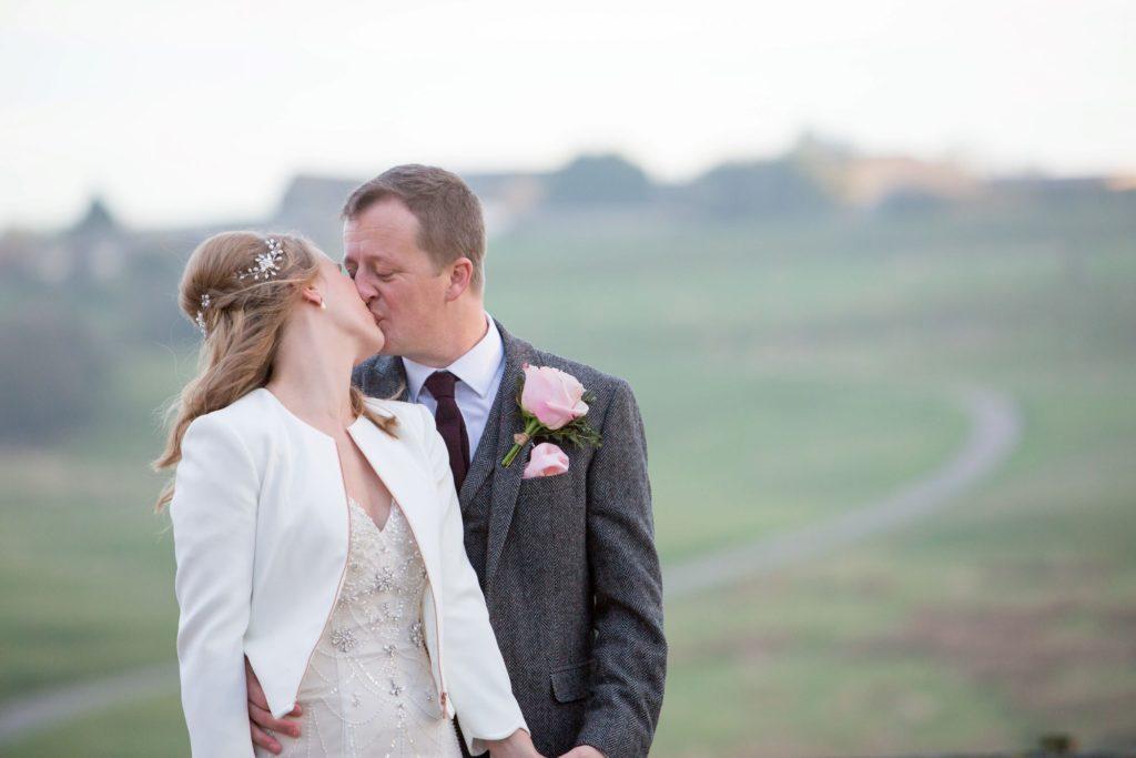 bride groom kiss kingscote barn grounds tetbury oxford wedding photographer