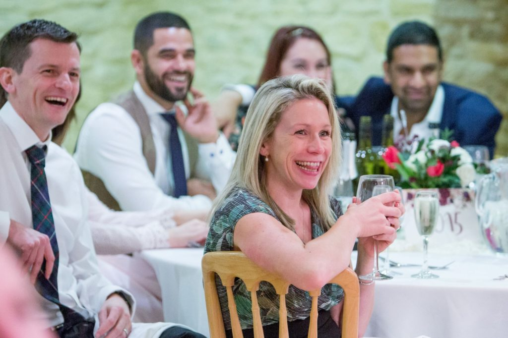 laughing guests kingscote barn tetbury reception dinner oxfordshire wedding photography