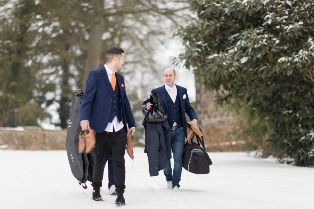 groom groomsmen trudge through winter snow berkeley castle stately home gloucestershire oxfordhire wedding photography