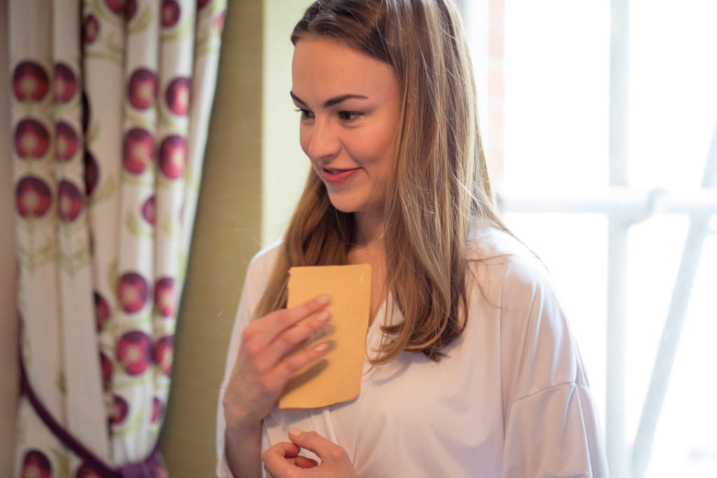 bride reads note during prep st ermins hotel westminster london oxford wedding photography