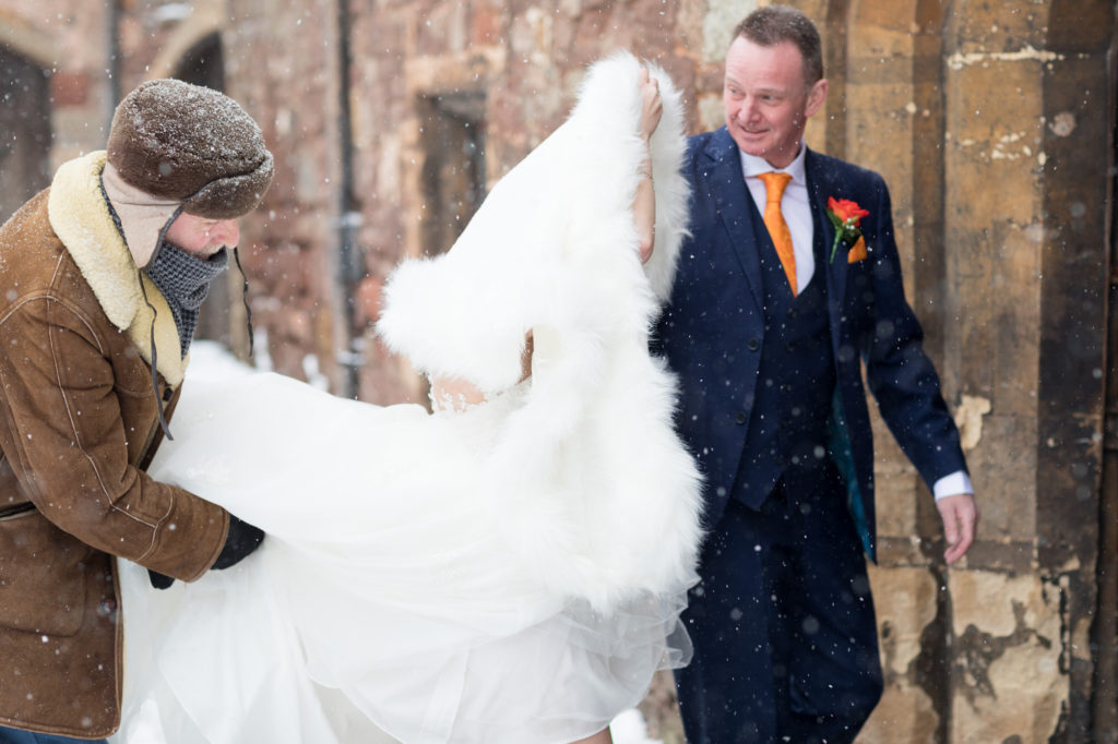 father of the bride with daughter in snow flurry berkeley castle stately home gloucestershire oxfordshire wedding photographer