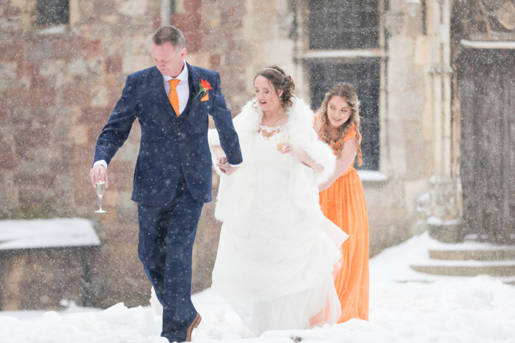 father of the bride and daughter battle through winter snow berkeley castle gloucestershire oxfordshire wedding photography