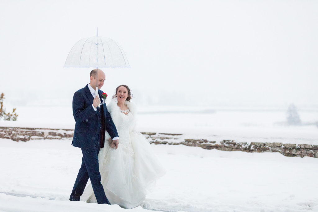 bride groom brolley stroll through winter snow berkeley castle gloucestershire oxfordshire wedding photography