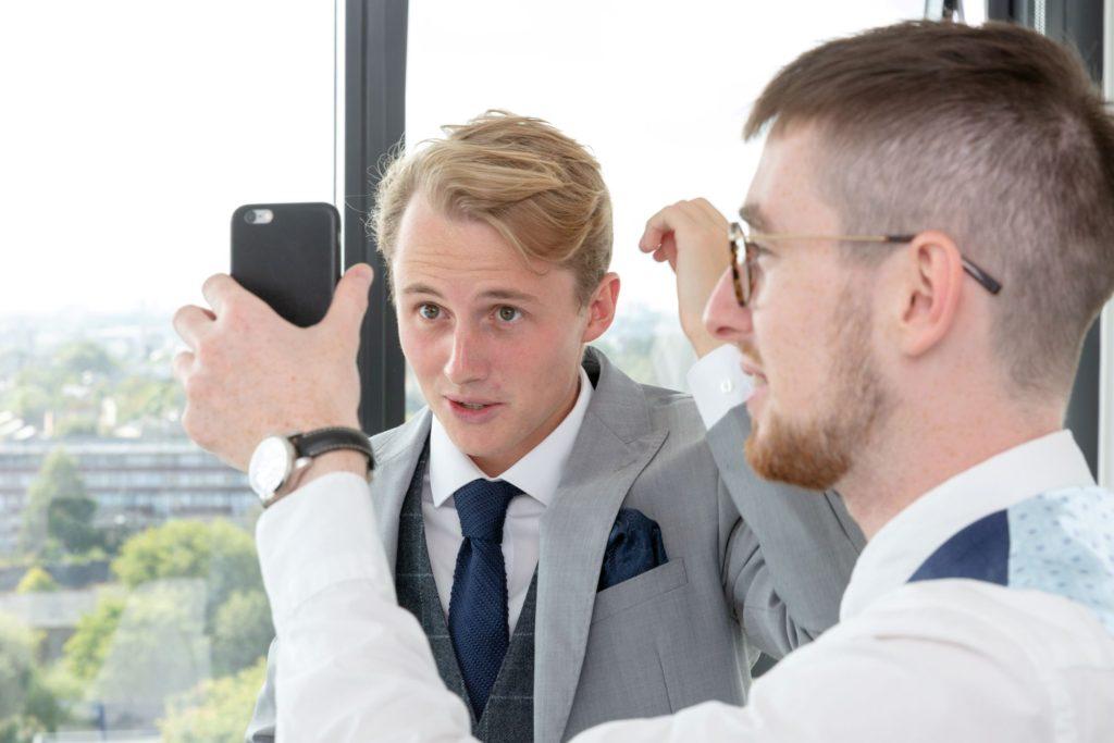 groom helps groomsman check hair st marys church marylebone london oxford wedding photography