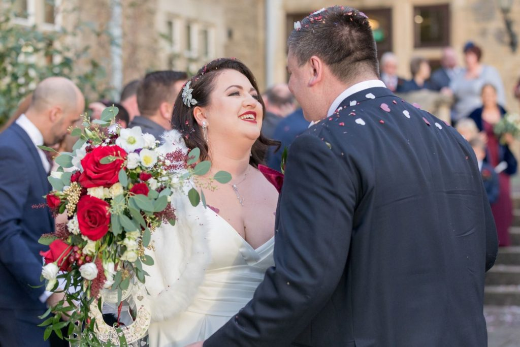 bride smiles at groom after confetti parade south lodge venue horsham oxford wedding photographer