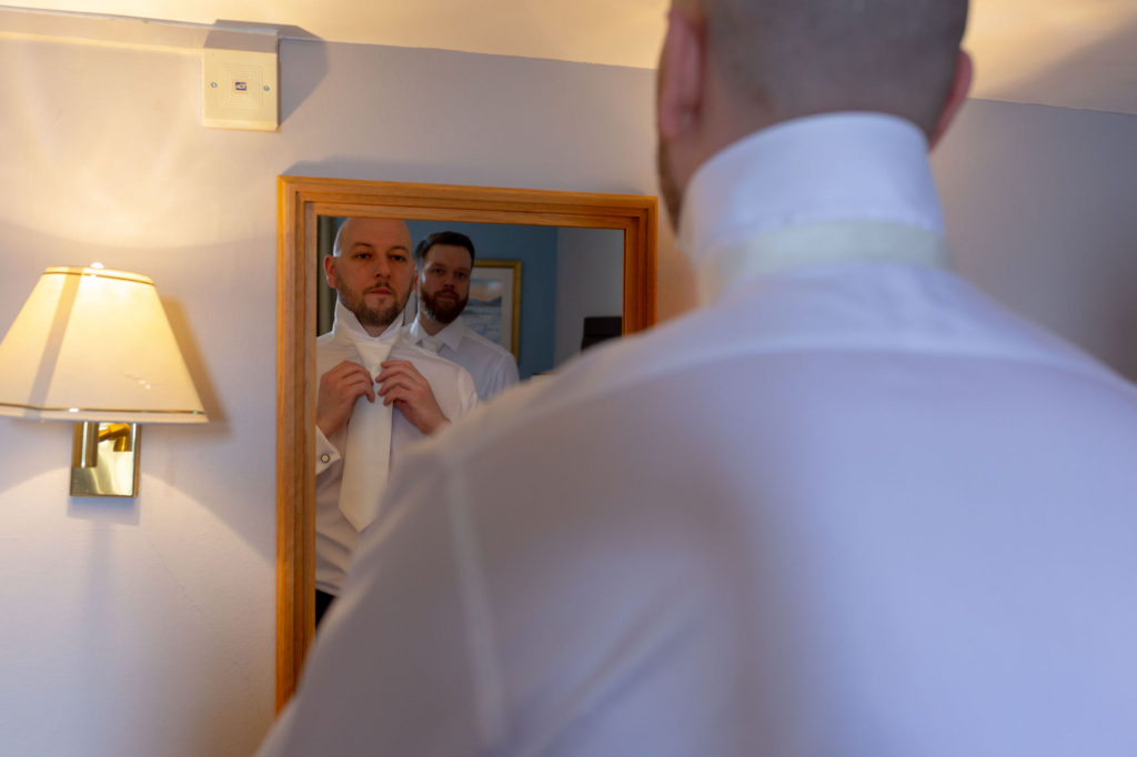 groom checks tie in mirror de vere selsdon estate prep oxfordshire wedding photographer