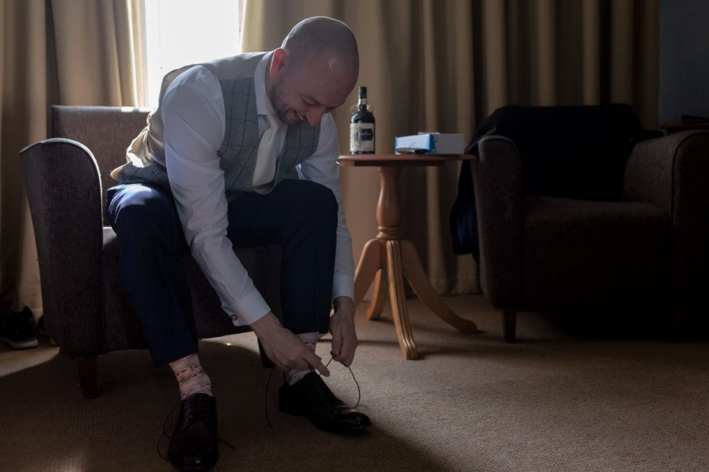groom prep shoe tying de vere selsdon estate venue croydon oxfordshire wedding photography