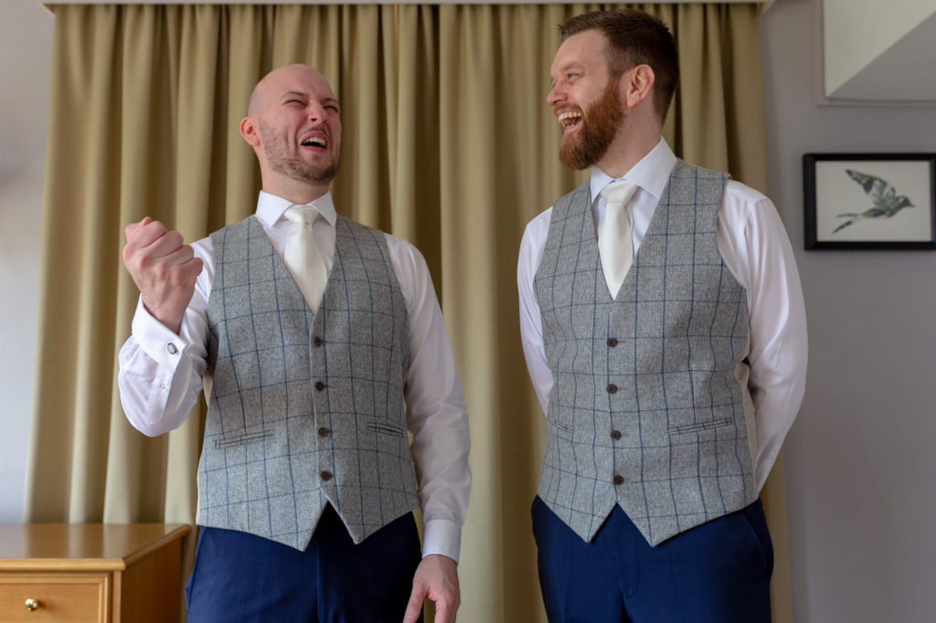 groom and bestman laugh during groom prep de vere selsdon estate croydon oxford wedding photography