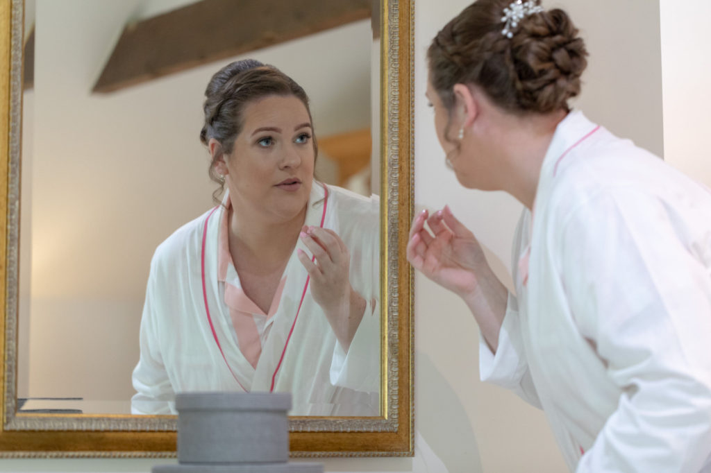 bride checks makeup in mirror bridal prep oaks farm wedding venue surrey oxford wedding photography