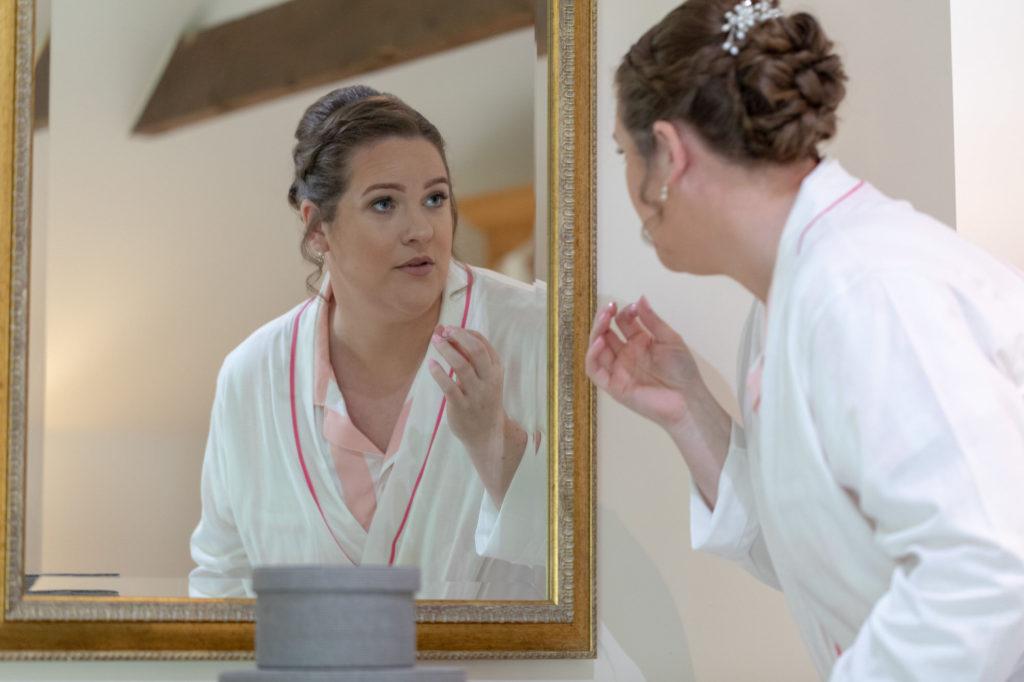 bride checks makeup in mirror bridal prep oaks farm wedding venue surrey oxford wedding photography