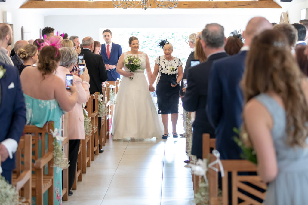 bride and mother walk down aisle oaks farm surrey oxford wedding photography
