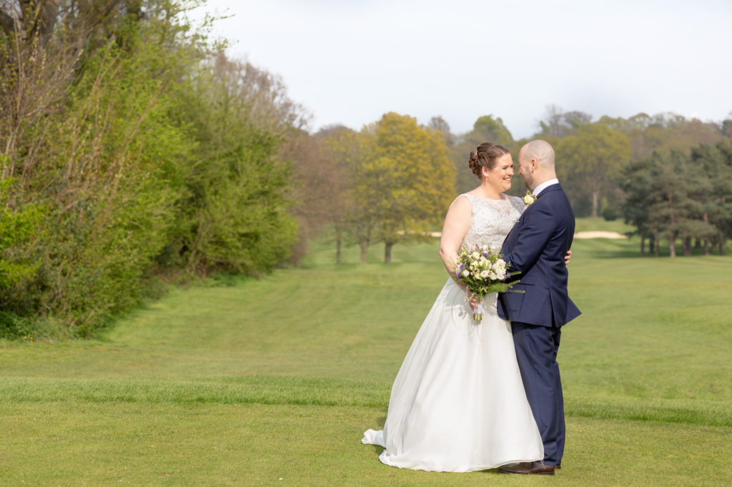 bride groom embrace on golf course oaks farm surrey oxfordshire wedding photography