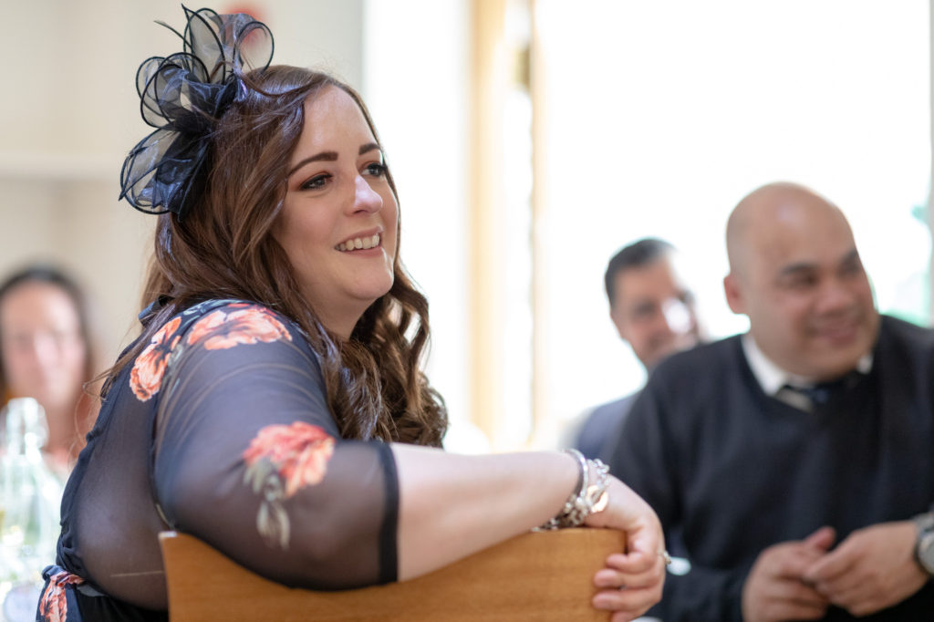 smiling guest listens to reception speech oaks farm wedding venue surrey oxfordshire wedding photographer