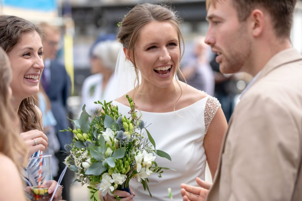 905 bride with bouquet laughs with reception guests st marys church marylebone london oxford wedding photographers
