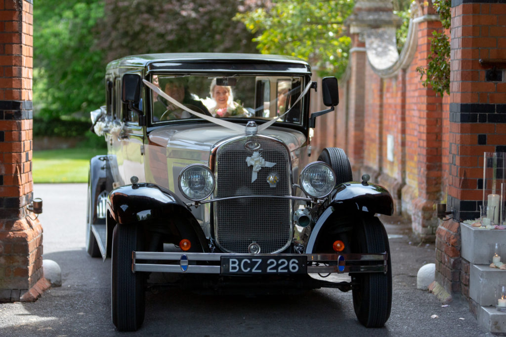 bridal classic car enters reception arch the elvetham hartley wintney hampshire oxfordshire wedding photographers