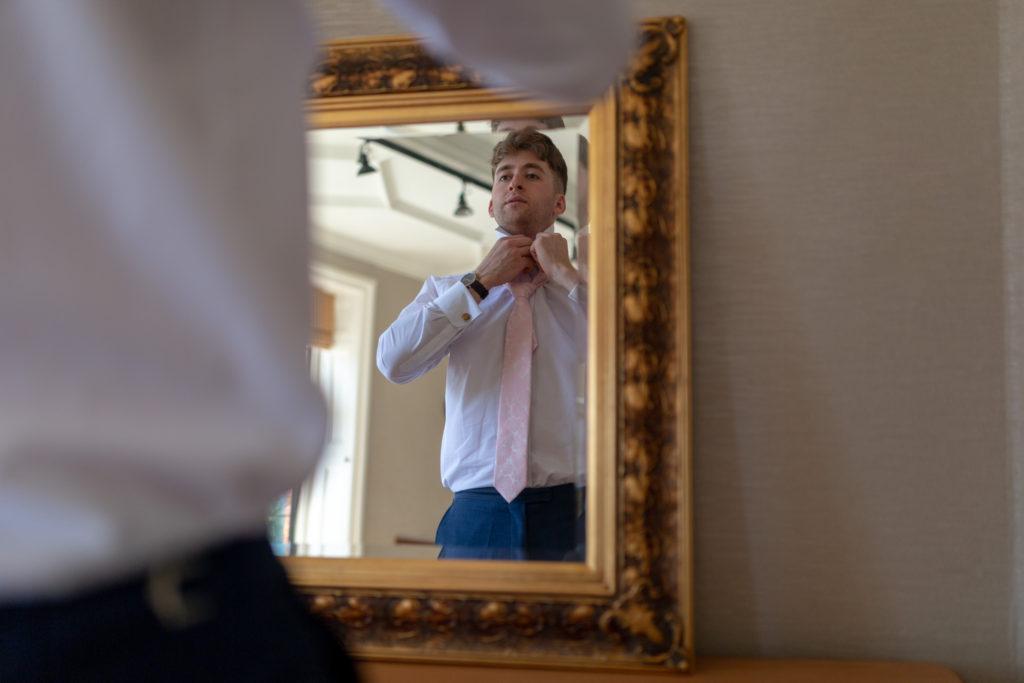 groomsman checks tie in mirror the elvetham hartley wintney hampshire oxfordshire wedding photographers