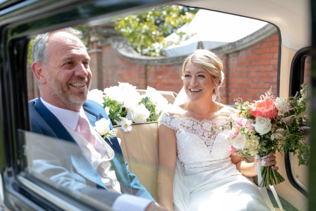 laughing bride with father of the bride in bridal car the elvetham hartley wintney hampshire oxford wedding photographers