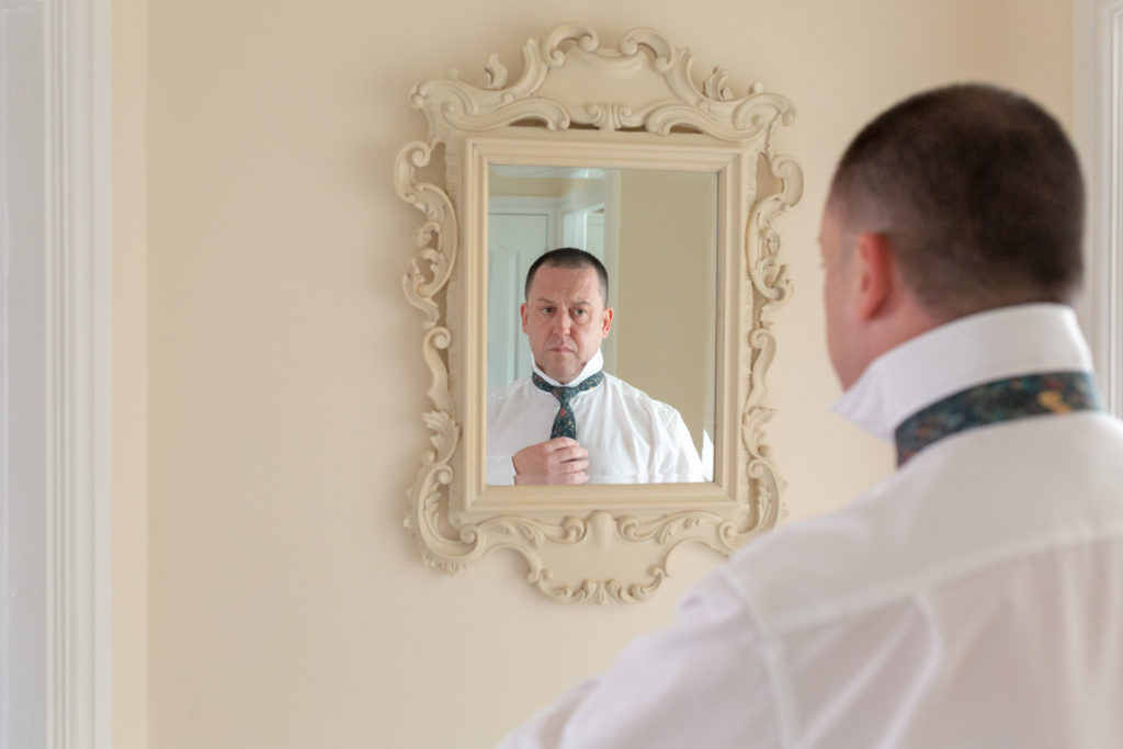 groom checks tie in mirror ardencote claverdon warwick venue oxford wedding photography