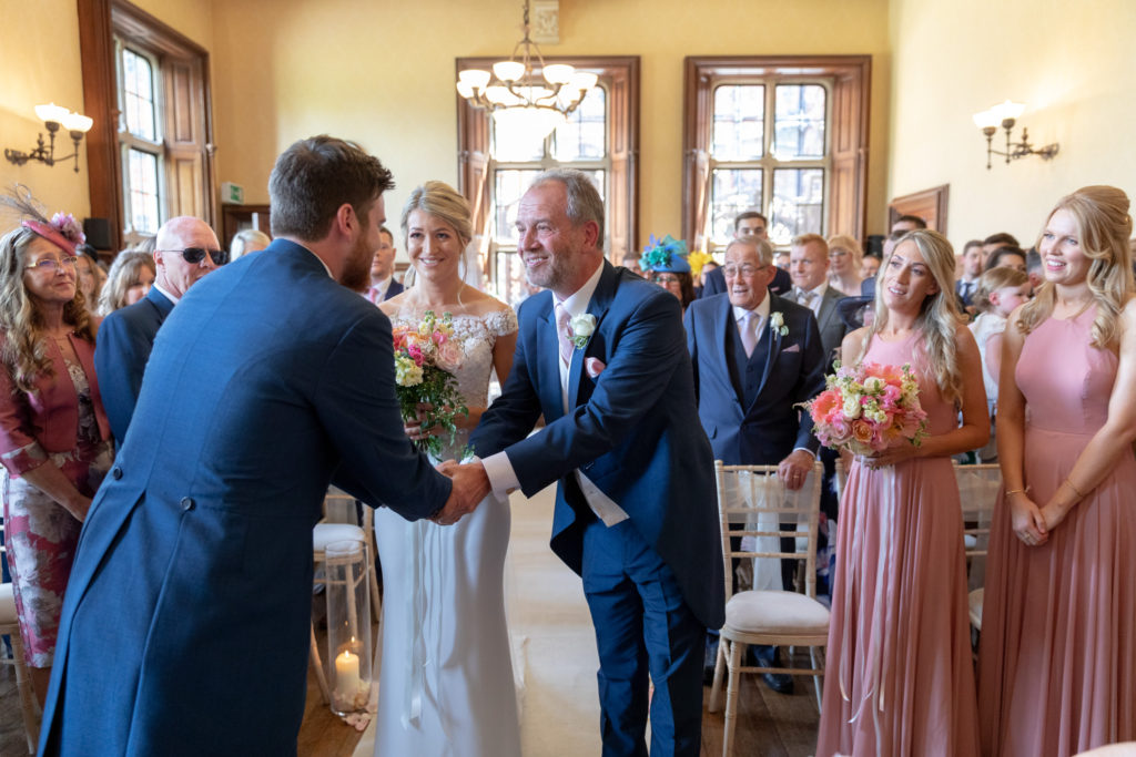 groom greets brides father marriage ceremony the elvetham hartley wintney hampshire oxfordshire wedding photographer