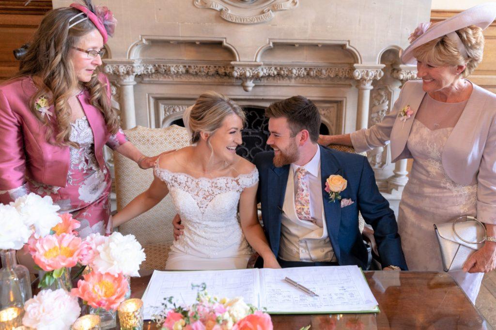 smiling bride groom sign register the elvetham hartley wintney hampshire oxford wedding photographers